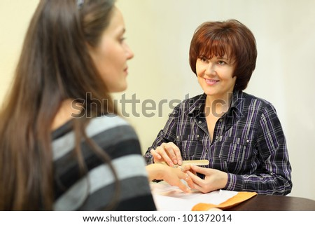 Smiling manicurist makes manicure by nailfile for woman in beauty salon; focus on manicurist - stock photo