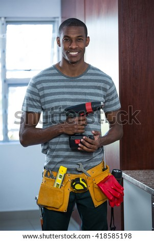 Smiling manual worker holding a drill machine at home