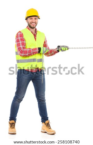 Smiling manual worker in yellow helmet and lime reflective vest pulling a chain. Full length studio shot isolated on white. - stock photo