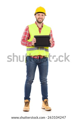 Smiling manual worker in yellow helmet and lime waistcoat holding shockproof digital tablet in both hands. Full length studio shot isolated on white.