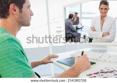 Smiling marketing manager standing in conference room against concentrated photo editor working on graphics tablet - stock photo