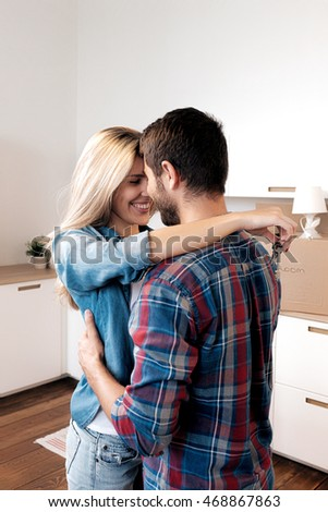 Smiling married couple hugging with keys in kitchen