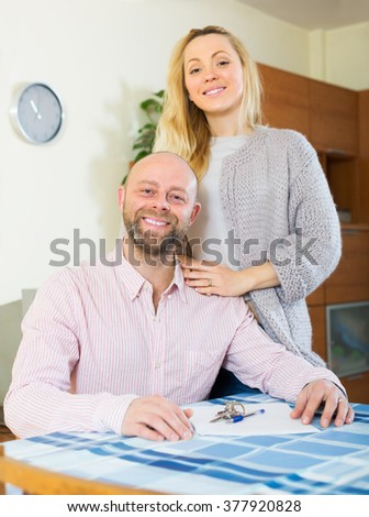 Smiling married couple sitting at table with keys and documents - stock photo