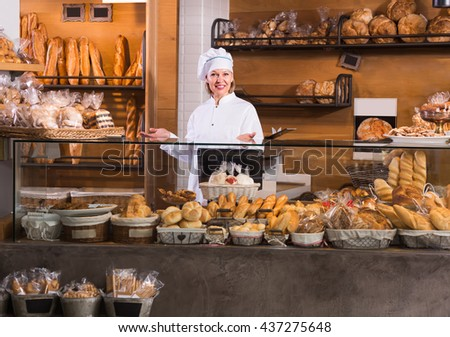 Smiling mature bakery employee offering bread and different pastry for sale
