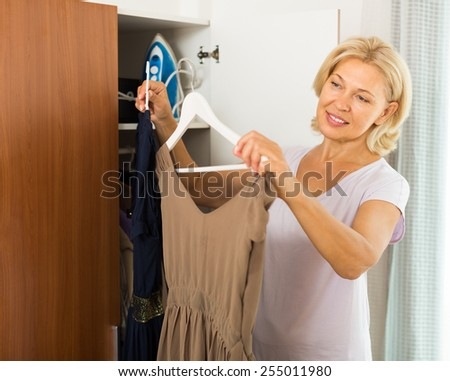 Smiling mature blonde woman choosing dress in wardrobe at her home  - stock photo