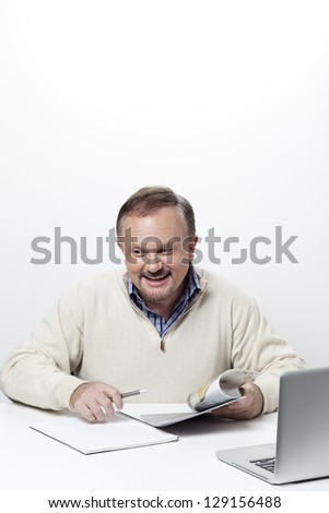 Smiling mature business holding a pen and a magazine
