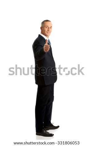 Smiling mature businessman gesturing ok sign.
