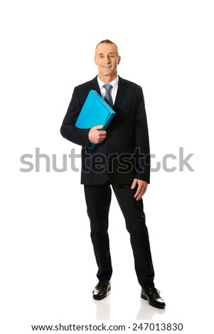 Smiling mature businessman holding a binder. - stock photo