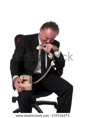 Smiling mature businessman holding a telephone receiver while sitting on a chair