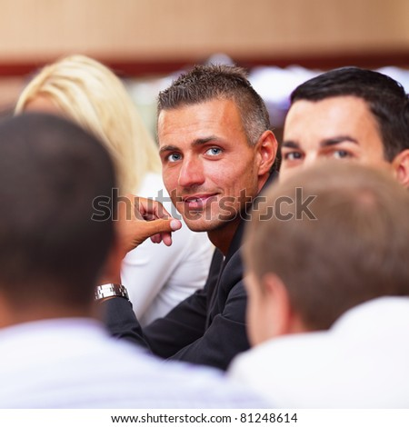 Smiling mature businessman sitting at a business meeting with colleagues - stock photo