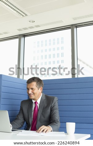 Smiling mature businessman using laptop at desk - stock photo