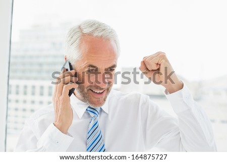 Smiling mature businessman using mobile phone as he clenches his fist in a bright office