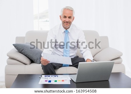 Smiling mature businessman working on graphs and laptop in the living room at home
