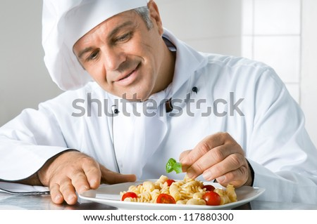 Smiling mature chef preparing an Italian dish of pasta with satisfaction