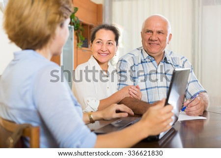 Smiling mature couple discussing for realtor at home - stock photo