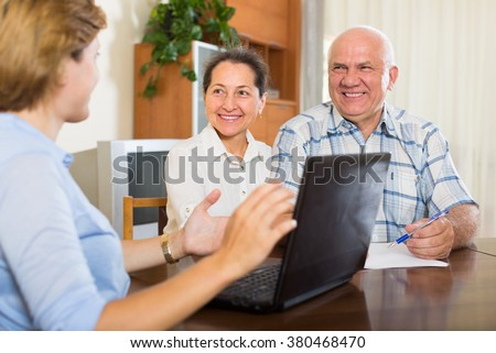 Smiling mature couple discussing for social worker of  company at home