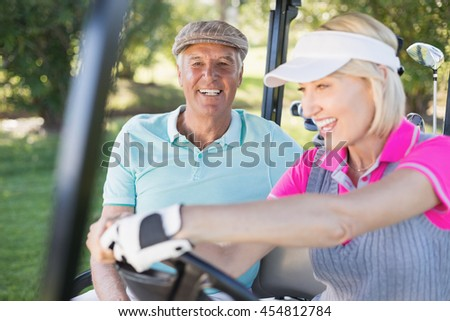 Smiling mature couple enjoying in golf buggy - stock photo