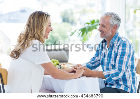 Smiling mature couple holding hands while sitting in restaurant - stock photo
