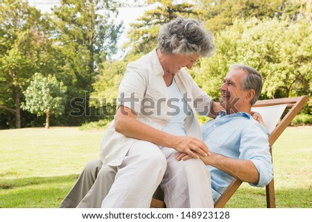 Smiling mature couple in park on sun lounger - stock photo