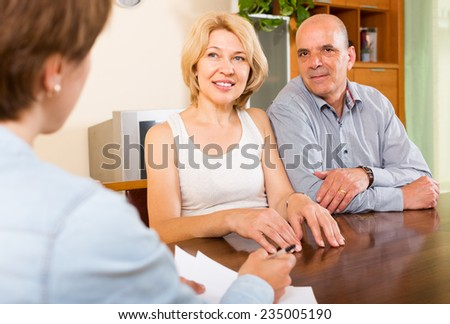 Smiling mature couple  talking with employee at office - stock photo