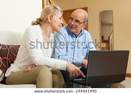 Smiling mature couple  with laptop  at table in home  - stock photo