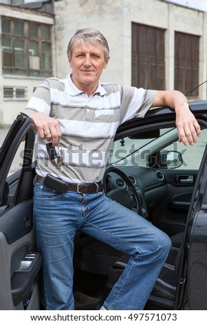 Smiling mature driver with ignition key in hand standing near own car