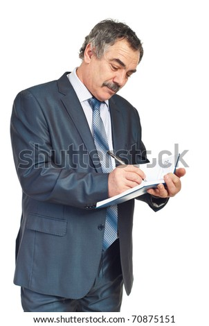 Smiling mature executive man taking notes in his personal agenda isolated on white background