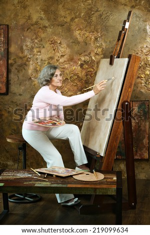 Smiling mature female artist painting at easel in art studio - stock photo