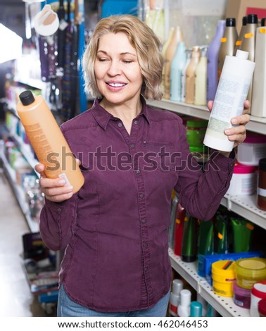 Smiling mature female customer buying volume shampoo in supermarket hair section