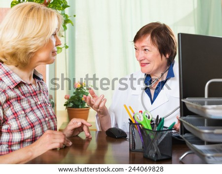 Smiling mature female doctor consulting patient in office - stock photo