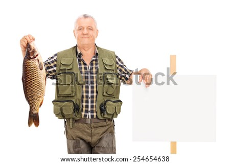 Smiling mature fisherman holding a big fish next to a panel isolated on white background - stock photo