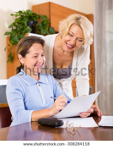 Smiling mature ladies signing documents at home. Focus on the woman on the left - stock photo