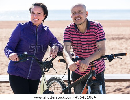Smiling mature man and woman holding their bicycles outdoor