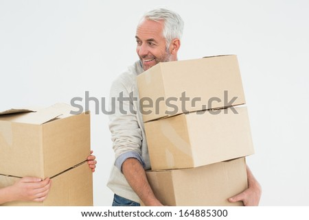 Smiling mature man carrying boxes against white background