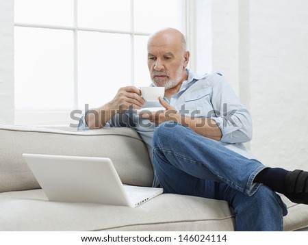 Smiling mature man drinking coffee while looking at laptop on sofa at home - stock photo