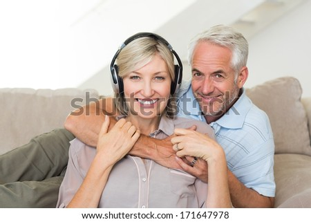 Smiling mature man embracing woman from behind on sofa at home
