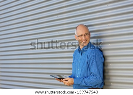 Smiling mature man holding digital tablet, outdoor - stock photo