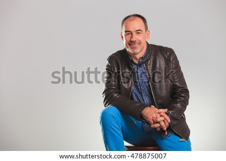 smiling mature man in leather jacket resting on a chair in studio