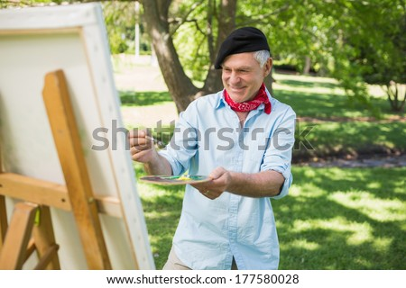 Smiling mature man painting on canvas in the park - stock photo