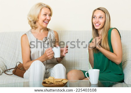 Smiling mature mother and adult daughter gossiping on sofa at home. Focus on mature - stock photo