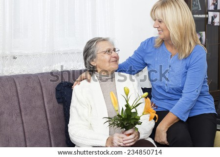 Smiling mature nurse sitting on the sofa and embracing senior woman ,  holding a bouquet of flowers. - stock photo