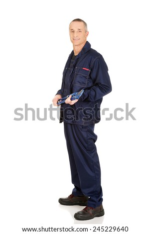 Smiling mature plumber holding a wrench. - stock photo