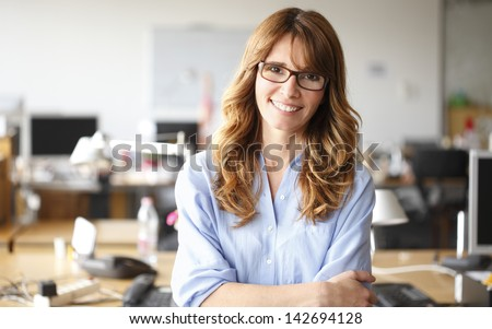 Smiling mature professional businesswoman in casual, with arms crossed standing in office. Shallow focus. - stock photo