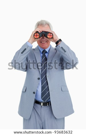 Smiling mature tradesman looking through spy glass against a white background - stock photo
