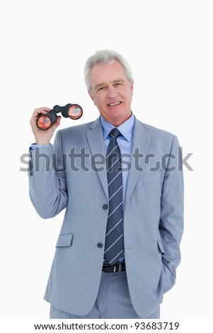 Smiling mature tradesman with spy glass against a white background - stock photo