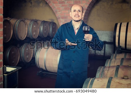 smiling mature winery employee holding wine sample in glass in cellar with woods