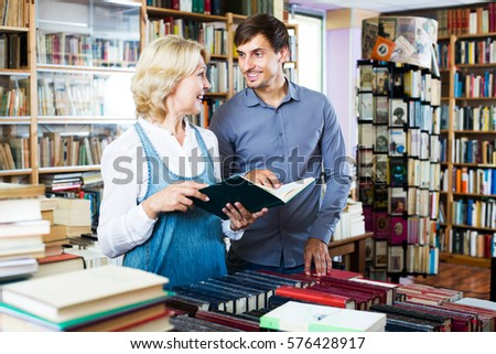 Smiling mature woman and young man having books in hands in book shop