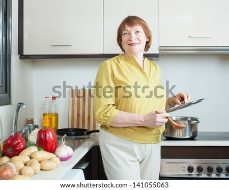 Smiling mature woman cooking in domestic kitchen