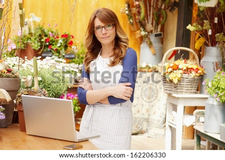 Smiling Mature Woman Florist Small Business Flower Shop Owner. Shallow Focus.  - stock photo
