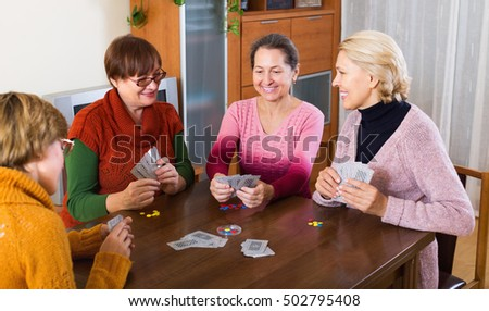 Smiling mature woman having fun with pack of cards indoor